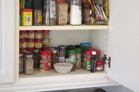 The before shot of our unorganized spice cabinet.